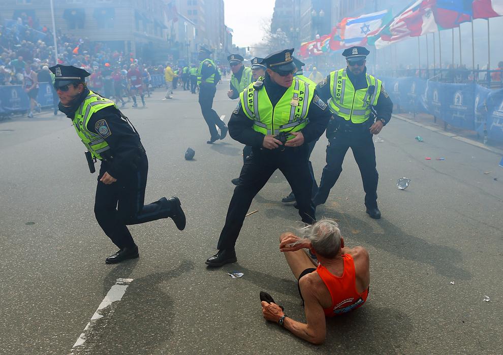 Ofiţeri de poliţie cu armele scoase din toc reacţionează în timpul celei de-a doua explozii, în Boston, luni, 15 aprilie 2013.