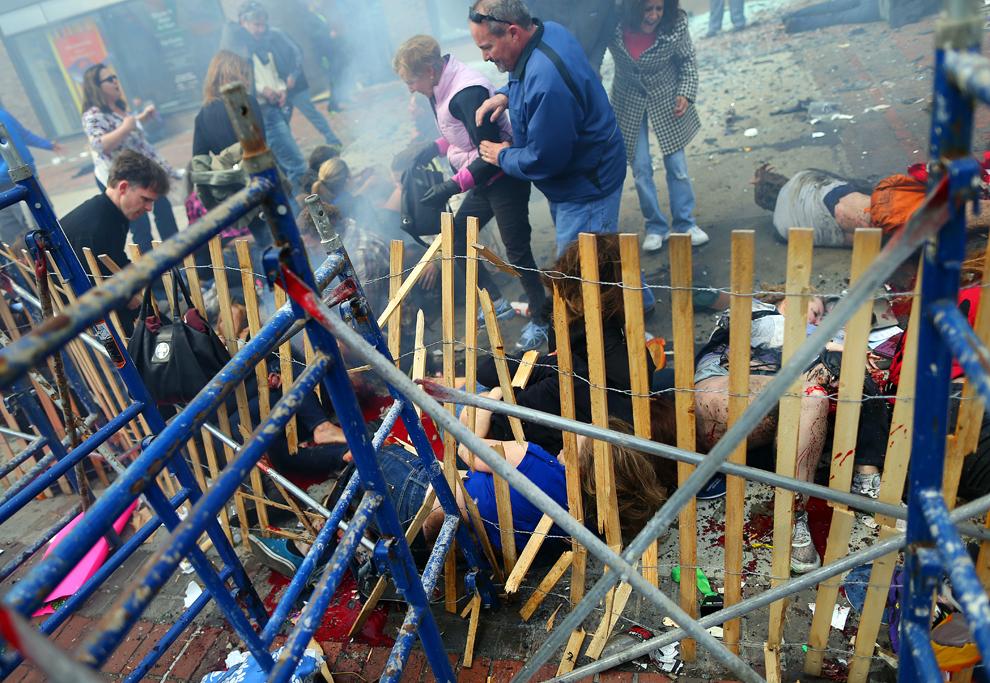 Persoane rănite aflate în stare de şoc aşteaptă să fie tratate, aproape de locul primei explozii, în Boston, luni, 15 aprilie 2013.