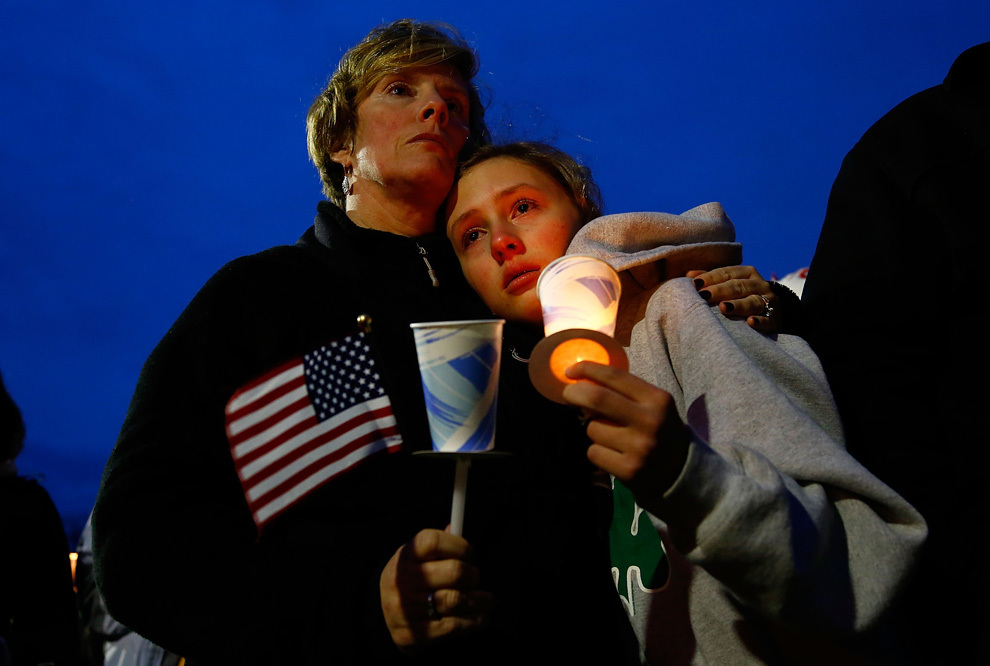 O tânără plânge alături de mama sa în timpul priveghiului lui Martin Richard, copilul în vârstă de 8 ani ucis de explozia unui dispozitiv improvizat la linia de sosire a Maratonului Boston, marţi, 16 aprilie 2013, în parcul Garvey din Boston, Massachusetts.