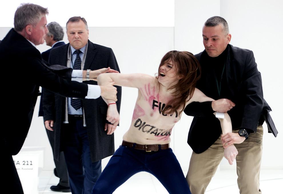 O protestatară topless este oprită de către forţele de securitate în timp ce se îndrepta către preşedintele rus, Vladimir Putin, şi cancelarul german, Angela Merkel, în timpul vizitei acestora la Târgul Industrial de la Hanovra, luni, 8 aprilie 2013.