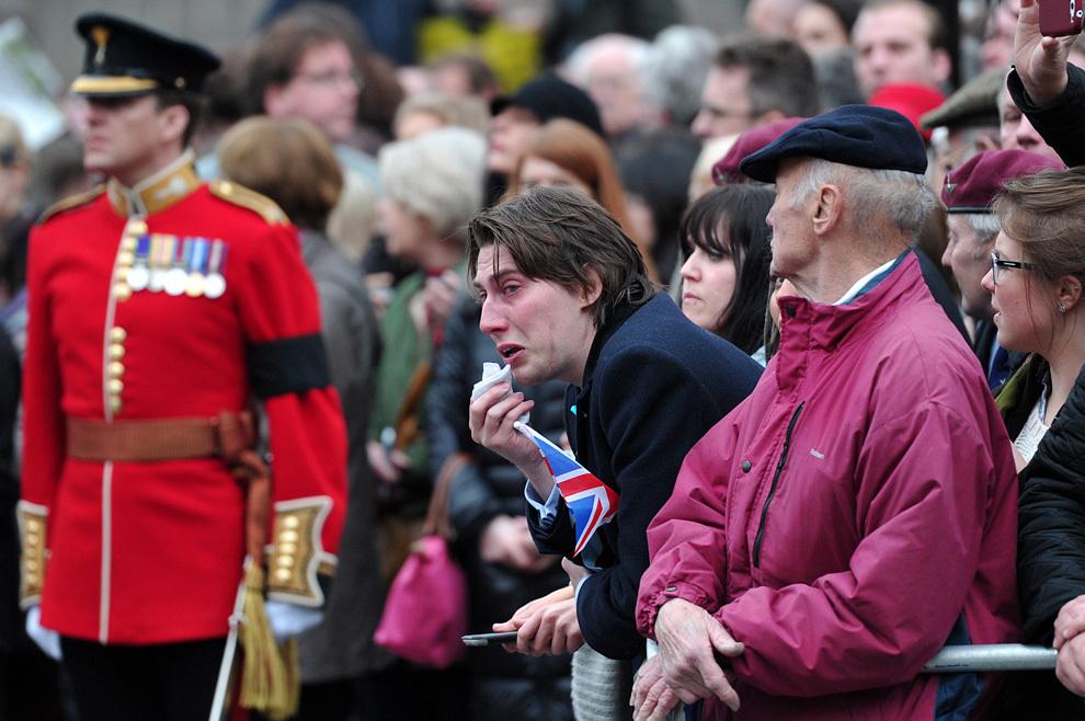Un bărbat reacţionează în timp ce sicriul cu trupul neînsufleţit al fostului premier britanic, Margaret Thatcher, este luat din biserica Saint Clement Danes, în timpul ceremoniei funerare, în centrul Londrei, miercuri, 17 aprilie 2013.