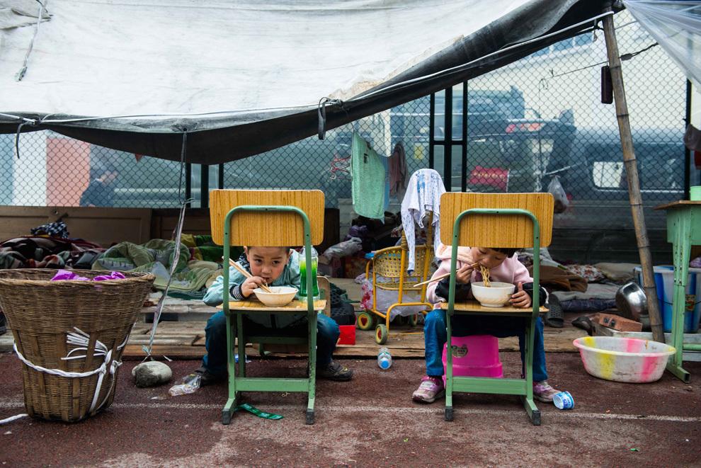 O fotografie realizată luni, 22 aprilie 2013, înfăţişează doi copii luând masa într-un adăpost temporar amenajat în Şcoala Generală Lingguan din Ya'an, în provincia Sichuan din sud-vestul Chinei. Zona muntoasă din sud-vestul Chinei a fost afectată de un puternic cutremur, care a produs cel puţin 188 de decese.