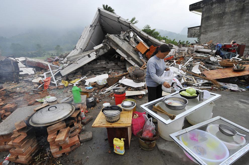 O fotografie realizată marţi, 23 aprilie 2013, înfăţişează o femeie gătind lângă ruinele unei case prăbuşite, în districtul Lushan din Ya'an, în provincia Sichuan din sud-vestul Chinei. Zona muntoasă din sud-vestul Chinei a fost afectată de un puternic cutremur, care a produs cel puţin 188 de decese.