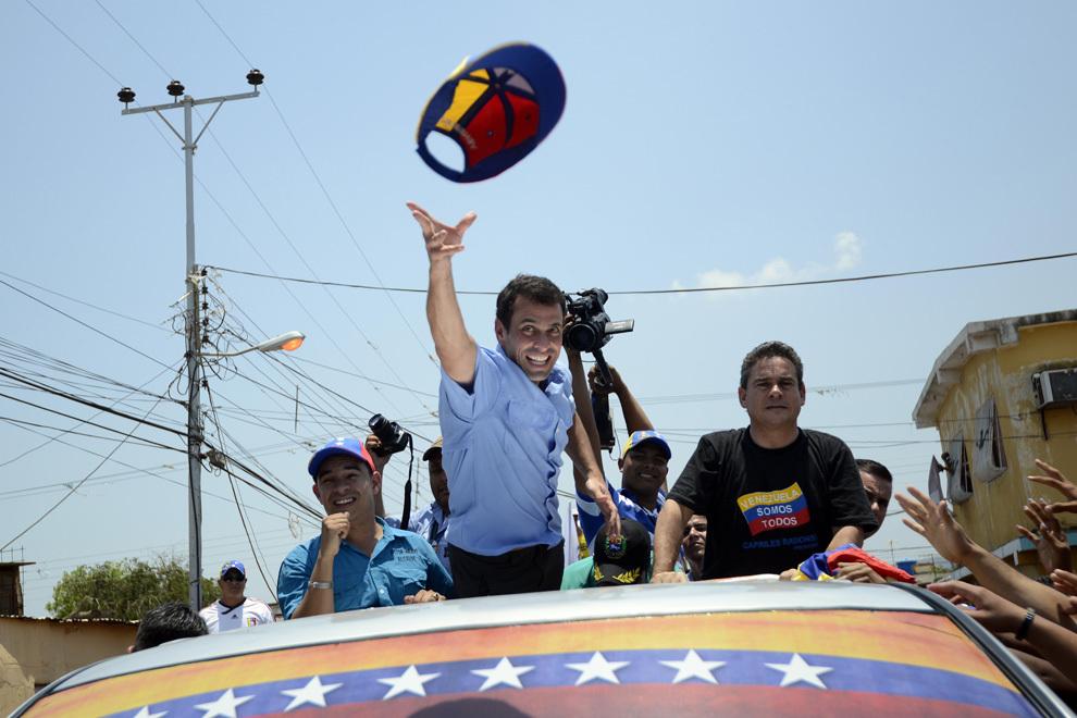 Liderul opoziţiei venezuelene Henrique Capriles (C) aruncă mulţimii şapca pe care o purta, în timpul unui miting electoral, în Coro, statul Falco, sâmbătă, 6 aprilie 2013.