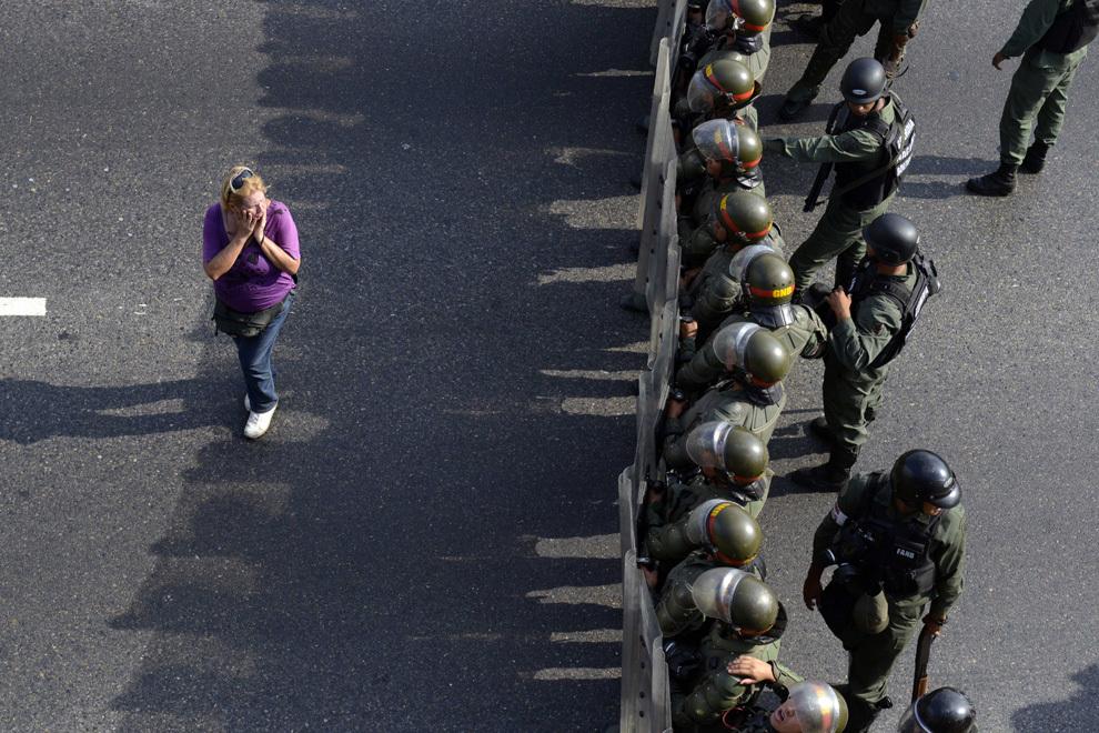 O femeie, susţinătoare a liderului opoziţiei venezuelene, Henrique Capriles, protestează în faţa scutierilor, în Caracas, luni, 15 aprilie 2013. Opoziţia venezueleană presează tot mai mult autoritatea electorală pentru a renumăra voturile rezultate în urma alegerilor care au avut loc pentru a-l înlocui pe fostul lider, Hugo Chavez.