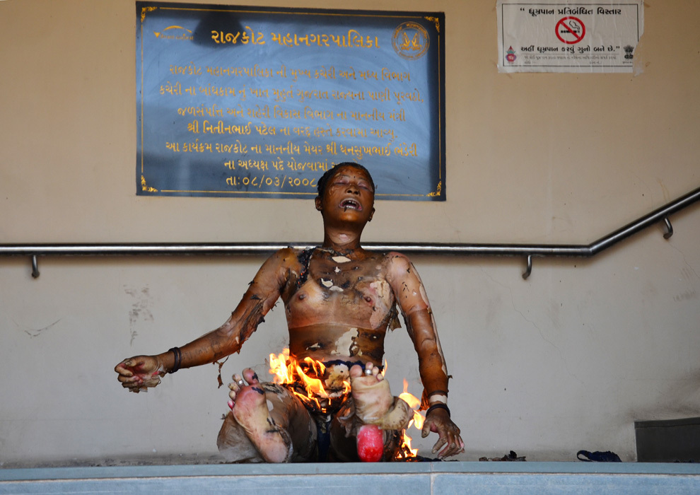 O fotografie realizată miercuri, 3 aprilie 2013, înfăţişează un protestatar indian care şi-a dat foc în faţa sediului primăriei din Rajkot, India,. Cinci persoane s-au autoincendiat în vestul Indiei, una dintre ele decedând, pentru a protesta împotriva planurilor oficiale de demolare a caselor construite ilegal.