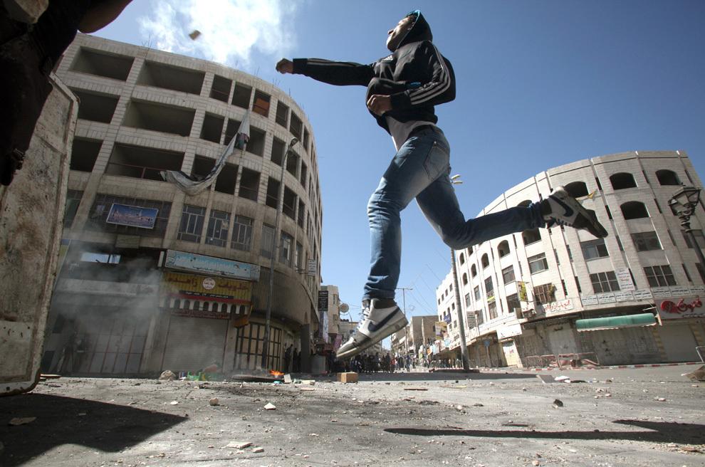 Un bărbat palestinian aruncă o piatră în direcţia forţelor de securitate israeliene, în timpul unor ciocniri în Hebron, Cisiordania, după moartea unui deţinut palestinian, marţi, 2 aprilie 2013.