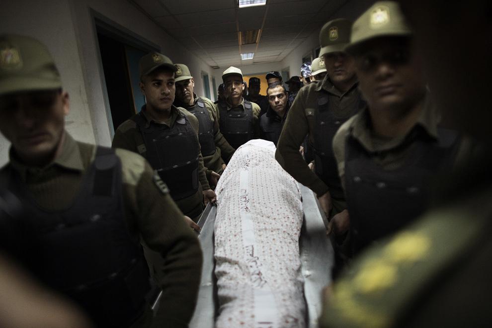 Soldaţi ai gărzii de onoare palestiniene ridică corpul lui Maisara Abu Hamdiyeh, prizonierul palestinian care a decedat în detenţie israeliană datorită unui cancer, din spitalul Al-Ahli din Hebron, Cisiordania, înaintea înmormântarii acestuia, joi, 4 aprilie 2013.