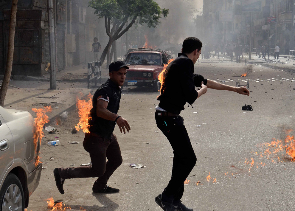 Creştini copţi egipteni încearcă să îşi stingă hainele arzând după ce au fost atacaţi de indivizi neidentificaţi, în faţa catedralei din cartierul central Abbassiya din Cairo, la sfârşitul funeraliilor a patru creştini ucişi în ciocnirile interconfesionale, duminică, 7 aprilie 2013.