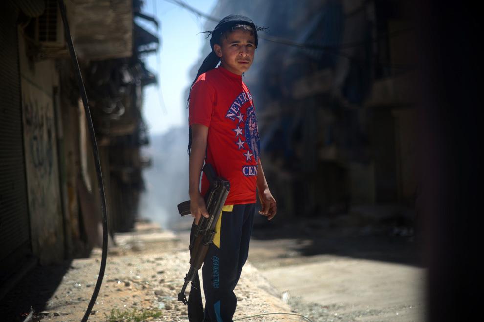 Un băiat sirian ţine o puşcă de asalt AK-47 pe o stradă din districtul majoritar kurd Shaikh Maqsud din Alep, duminică, 14 aprilie 2013.