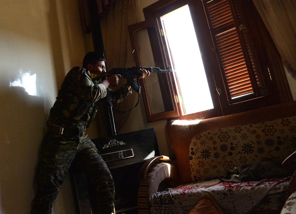 Un luptător kurd aparţinând 'Unităţilor de Protecţie Populară' (UPP) trage asupra forţelor guvernamentale siriene dintr-o clădire aflată în districtul majoritar kurd Shaikh Maqsud din Alep, duminică, 21 aprilie 2013.