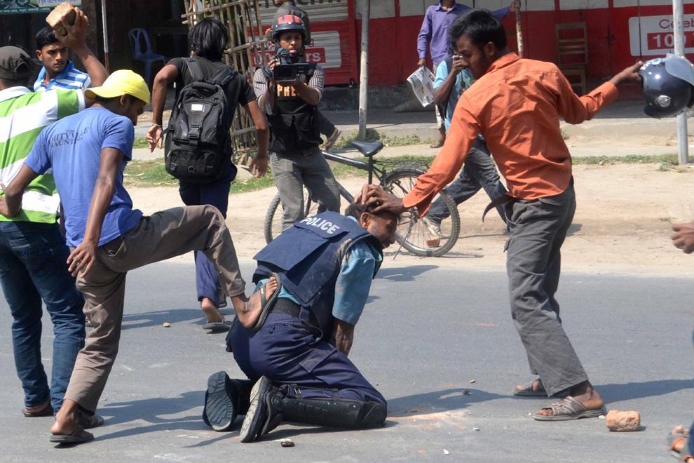 Studenţi aparţinând aripii din Bangladesh a partidului islamist Jamaat-e-Islami lovesc un ofiţer de poliţie, în oraşul Rajshahi din nord-vestul Bangladeshului, aflat la 260 de km de capitala Dhaka, luni, 1 aprilie 2013.