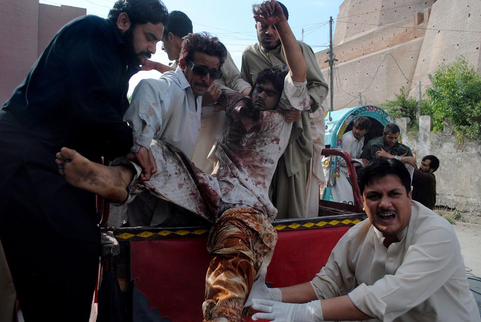 Mai mulţi bărbaţi pakistanezi urcă un bărbat rănit într-un autovehicul, pentru a-l transporta la spital, după explozia unei bombe într-un autobuz cu călători,  în Peshawar, sâmbătă, 13 aprilie 2013.