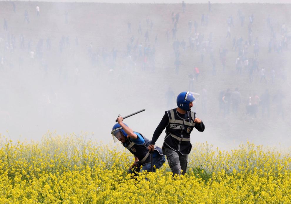 Un scutier turc loveşte un protestatar într-un câmp de rapiţă, în timpul unei demonstraţii organizate la universitatea Dicle din Diyarbakir, marţi, 9 aprilie 2013. Studenţii kurzi de stânga au protestat după o ciocnire între grupările de stânga şi de dreapta din cadrul universităţii Dicle.