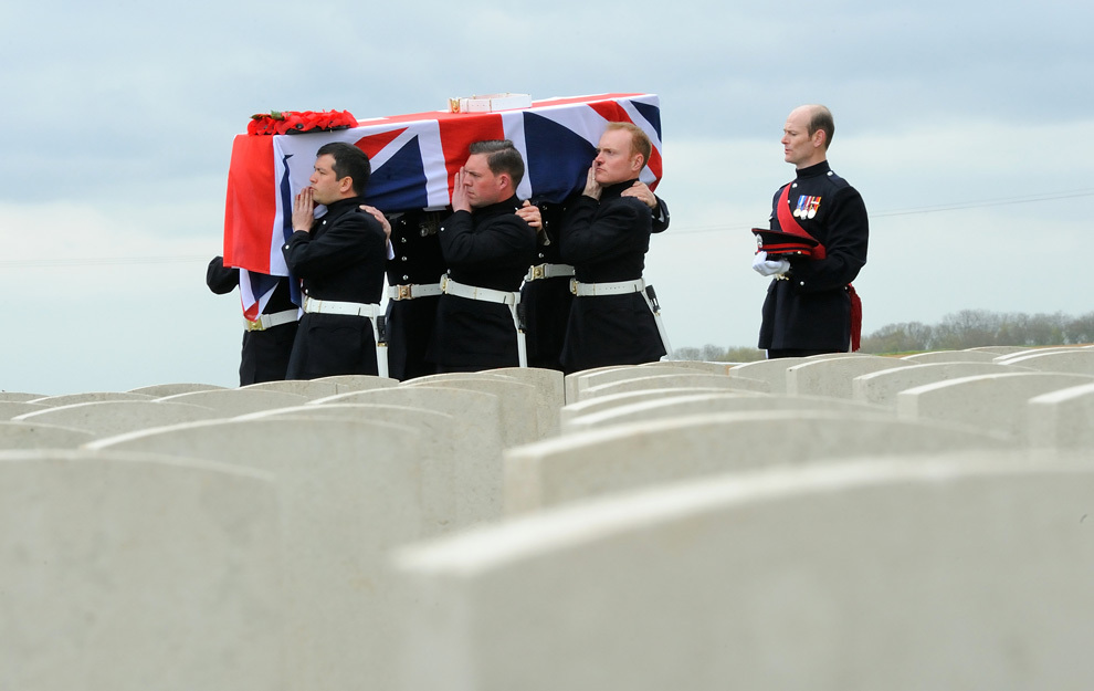 Sicriul conţinând rămăşiţele unui soldat britanic este purtat de către soldaţi ai gărzii de onoare în cimitirul Companiei Onorabile de Artilerie din Ecoust-Saint-Mein, Franţa. Patru soldaţi britanici au fost îngropaţi cu onoruri militare la aproape un secol după ce au decedat, în timpul Primului Război Mondial.