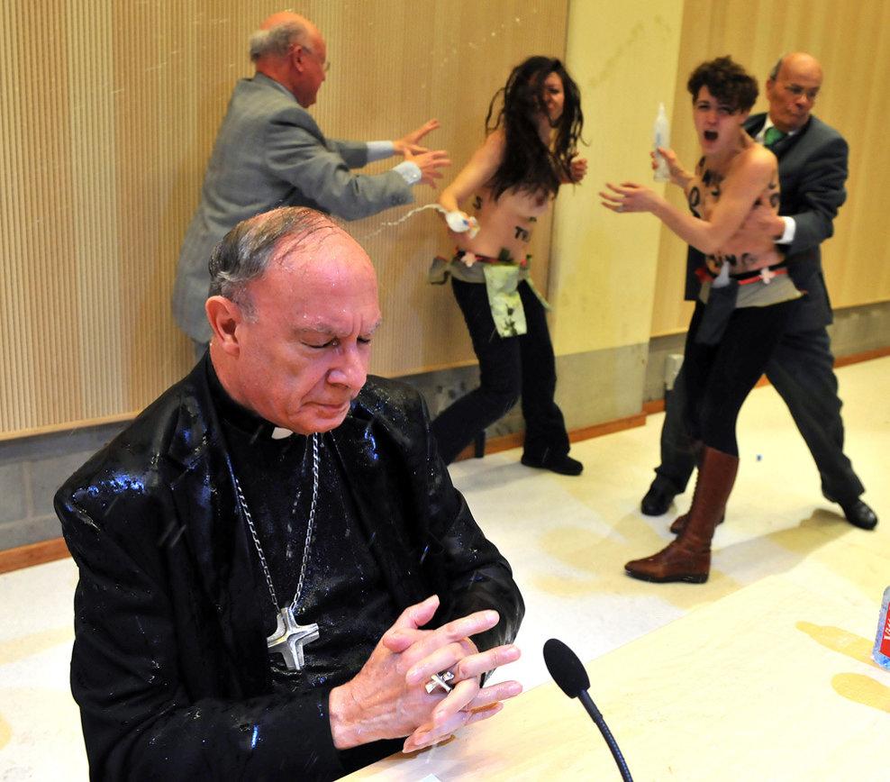 Arhiepiscopul Andre-Joseph Leonard este udat cu apă de către membre ale organizaţiei pentru drepturile femeilor Femen, care protestează împotriva homofobiei, în timpul unei prelegeri despre blasfemie, la universitatea ULB din Bruxelles, marţi, 23 aprilie 2013.