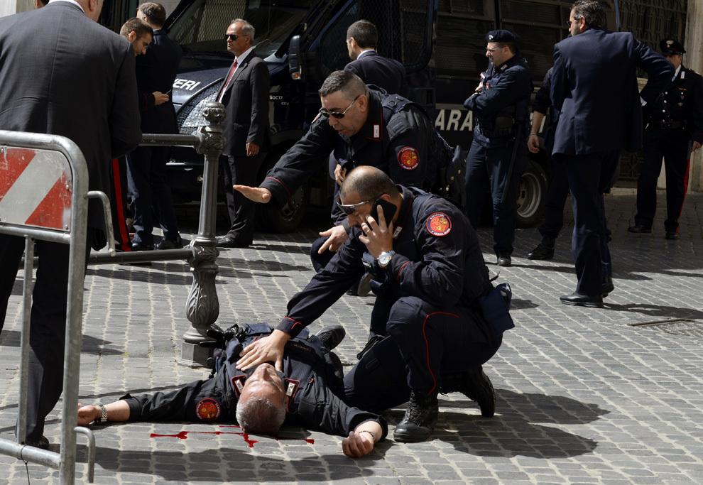 Un poliţist este ajutat după ce a fost împuşcat de un bărbat cu aparente probleme psihice, în faţa palatului Chigi, sediul şefului guvernului italian, în timp ce noii miniştri depun jurământul, în Roma, duminică, 28 aprilie 2013.