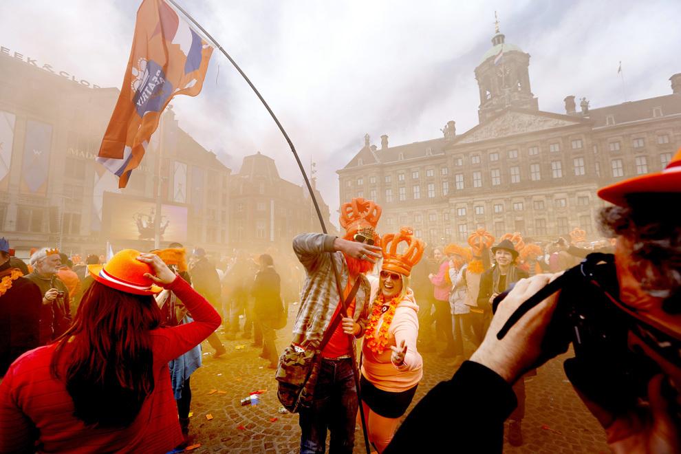 Mai multe persoane, unii purtând coroane din plastic gonflabile, sărbătoresc încoronarea noului rege în Piaţa Dam din Amsterdam, marţi, 30 aprilie 2013. Prinţul moştenitor olandez Willem-Alexander a devenit cel mai tânăr monarh european, după ce mama sa, Regina Beatrix, a abdicat joi.