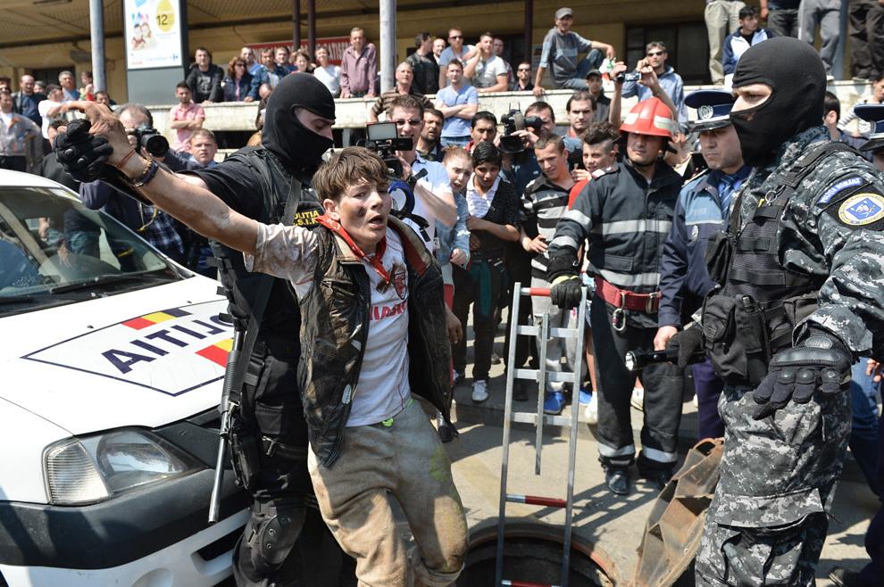 Un poliţist scoate dintr-un canal un om al străzii, în zona Gării de Nord din Bucureşti, miercuri, 24 aprilie 2013. Poliţiştii şi jandarmi bucureşteni au descins în canalele din zona Gării de Nord, unde ar fi fost ascunse de către oamenii străzii bunuri furate dintr-o locuinţă.