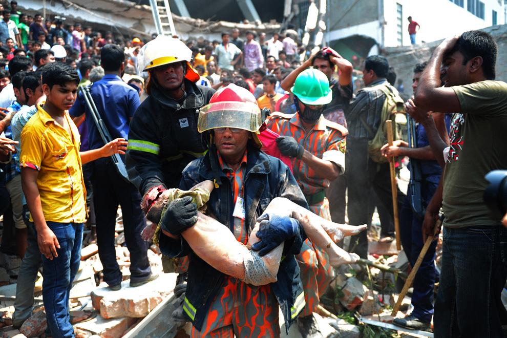 Un pompier ţine în braţe cadavrul unui copil, scos de sub dărâmăturile unei clădiri de 8 etaje care s-a prăbuşit în Savar, la periferia oraşului Dhaka din Bangladesh, miercuri, 24 aprilie 2013. Cel puţin 82 de persoane au decedat si 700 au fost rănite.