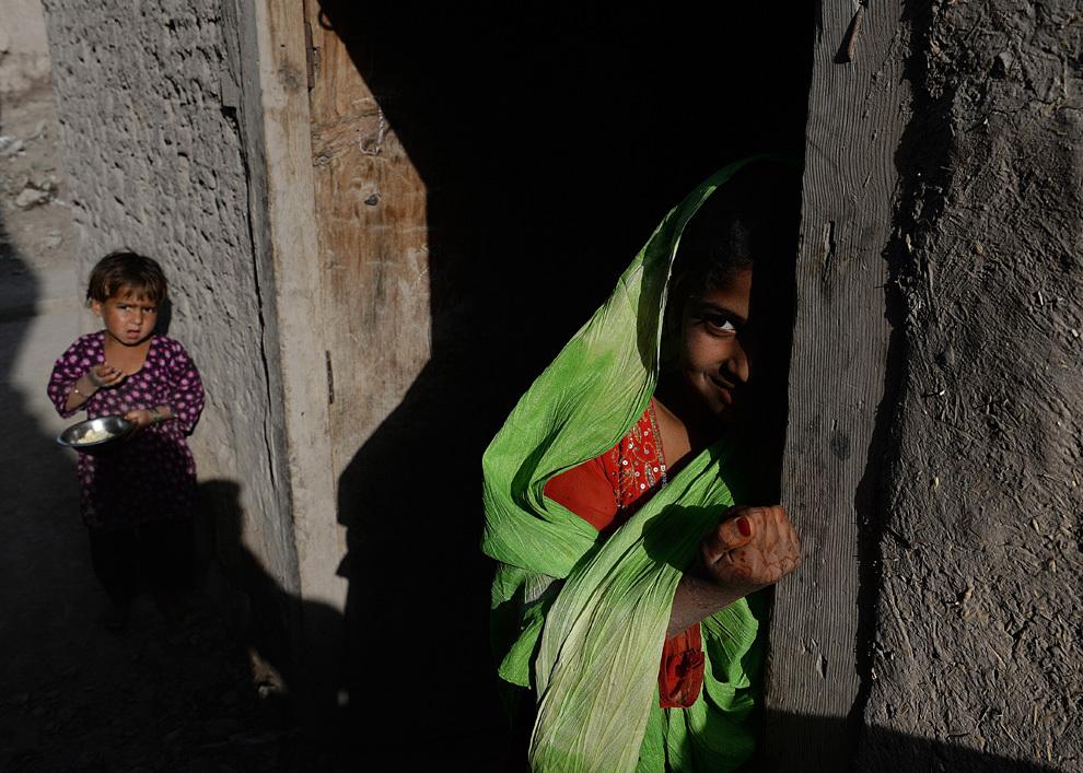 Două fetiţe afgane privesc din pragul casei distruse de un puternic cutremur, în satul Charbagh din provincia Nangarhar, miercuri, 24 aprilie 2013. Şapte persoane au fost ucise şi mai multe rănite de puternicul cutremur care a lovit estul Afganistanului.
