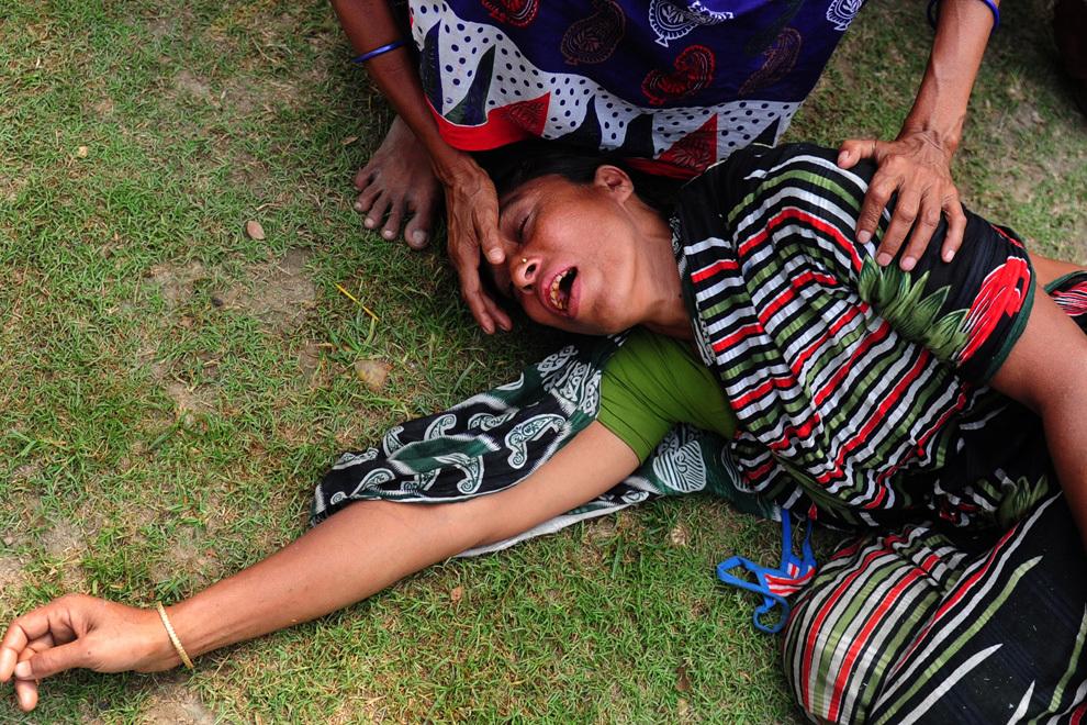 O femeie reacţionează după identificarea cadavrului soţului, recuperat dintre ruinile unei clădiri de 8 etaje care s-a prăbuşit în Savar, la periferia oraşului Dhaka, joi, 25 aprilie 2013. Numărul total al victimelor celui mai mare dezastru industrial din Bangladesh a ajuns la 200.