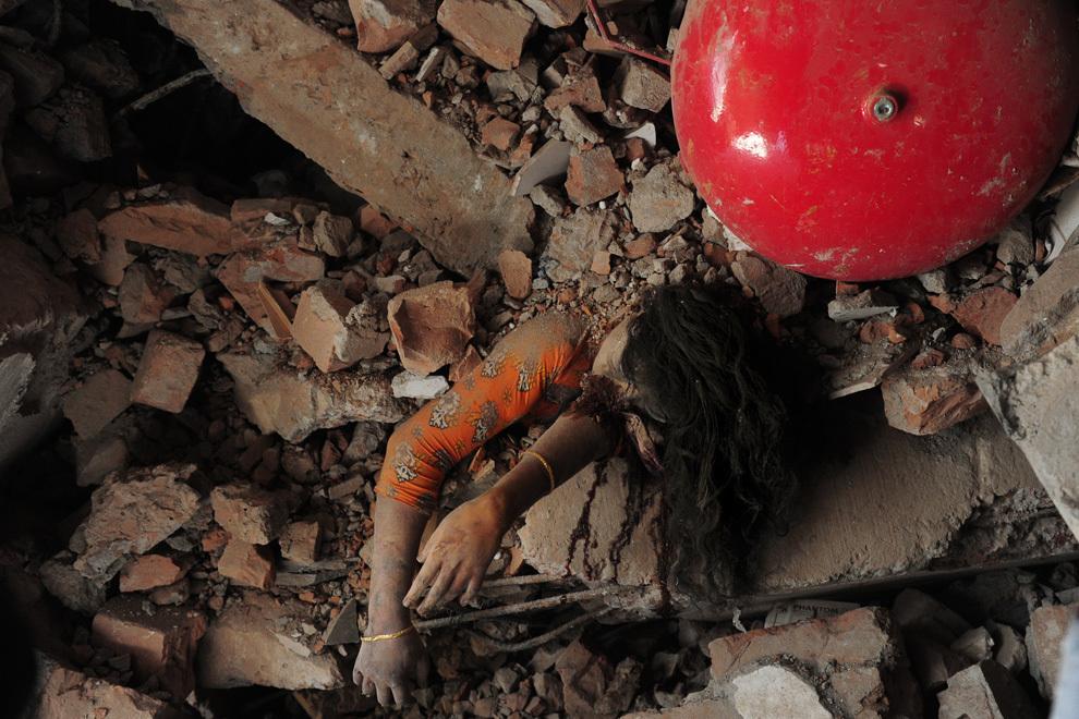 O muncitoare dintr-o fabrică de îmbrăcăminte zace zdrobită sub ruine, la 48 de ore după prăbuşirea clădirii de 8 etaje în care muncea, în Savar, la periferia oraşului Dhaka, vineri, 26 aprilie 2013. La locul dezastrului au fost descoperite aproape 300 de cadavre.
