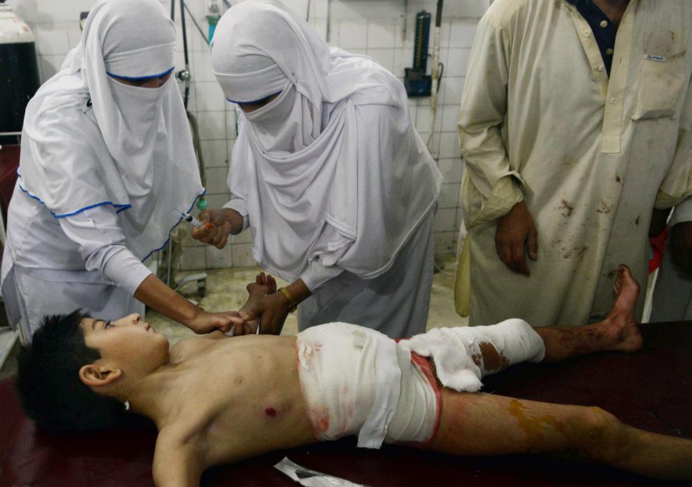 Paramedici pakistanezi tratează un copil, victimă a unui atentat cu bombă, în Peshawar, duminică, 28 aprilie 2013. Două atentate cu bombă, care vizau birourile electorale a doi candidaţi din nord-estul Pakistanului, au ucis, protrivit oficialilor, cel puţin 8 persoane.