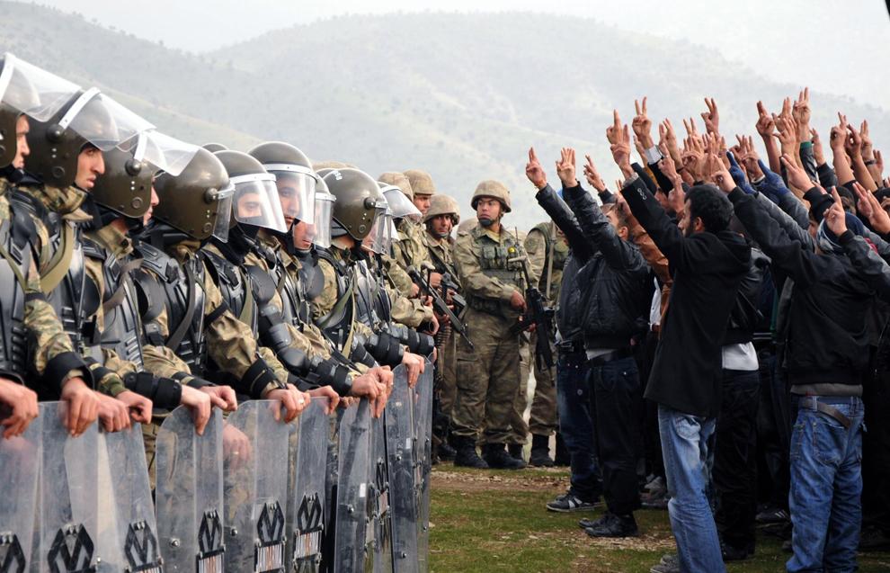 Manifestanţi kurzi protestează în faţa unui grup de soldaţi turci, în provincia Sirnak din Turcia, duminică, 14 noiembrie 2012. Guvernul turc a trimis parlamentului un proiect de lege care acordă kurzilor dreptul de a folosi propria limbă în instanţele de judecată, o solicitare cheie a sutelor de prizonieri aflaţi în greva foamei de 2 luni.