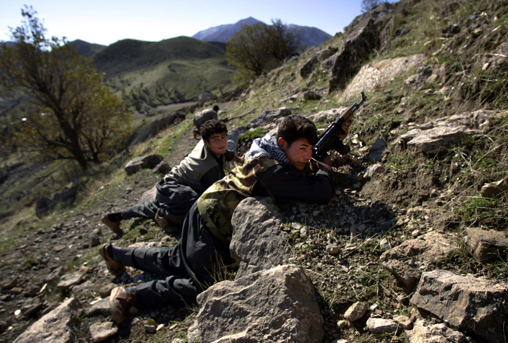 Luptători de gherilă ai Partidului Muncitorilor din Kurdistan se adăpostesc în timpul unei patrulări printr-o trecătoare montană, de-a lungul graniţei dintre Irak şi Iran, în munţii din nordul Kurdistanului Irakian, luni, 20 noiembrie 2006.