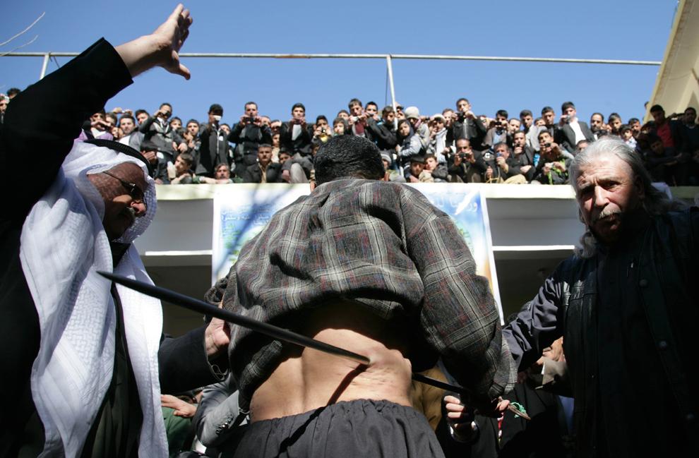 Un sufist kurd irakian introduce un obiect ascuţit din fier prin pielea unui credincios, în timpul unei ceremonii de comemorare a naşterii profetului Mahomed, în oraşul kurd Akra, la 500 de km nord de Bagdad, duminică, 5 februarie 2012.