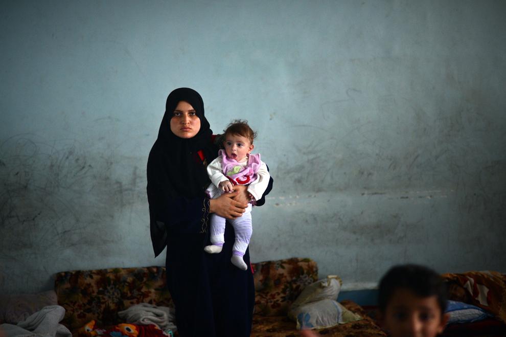 O refugiată kurdă din districtul Sheikh Maqsud al oraşului sirian Alep îşi ţine în braţe copilul într-o şcoală transformată în tabără pentru refugiaţi, în oraşul nordic majoritar kurd Afrin, marţi, 9 aprilie 2013. Ca urmare a luptelor care au atins şi zonele majoritar kurde ale Alepului, pâna de curând calme, mii de refugiaţi au ales să se retragă în micul oraş Afrin, aflat la 60 de km nord de capitala economică a Siriei.