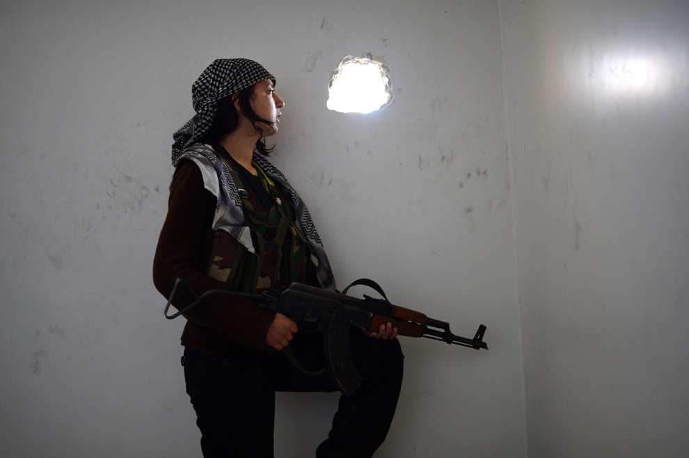 O luptătoare kurdă urmăreşte mişcările forţelor guvernamentale siriene în districtul majoritar kurd Sheikh Maqsud din oraşul sirian Alep, duminică, 14 aprilie 2013.