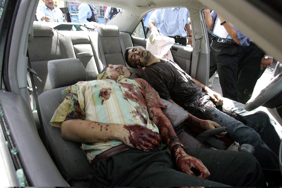 Cadavrele a doi bărbaţi kurzi, gărzile de corp ale deputatului kurd Fraidun Abdulqader, pot fi văzute în autovehiculul în care au fost împuşcaţi, în districtul sudic Dura al Bagdadului, miercuri, 8 iunie 2005.