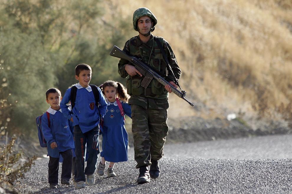 Un soldat turc patrulează, alături de trei copii aflaţi în drum spre şcoală, pe un drum din provincia Sirnak, în apropierea graniţei dintre Turcia si Irak, miercuri, 17 octombrie 2007. Vicepreşedintele iraqian Tareq al-Hashemi a vorbit miercuri de 'o nouă atmosferă' în eforturile diplomatice realizate pentru a preveni o incursiune militară turcă împotriva bazelor rebele kurde din nordul Iraqului.