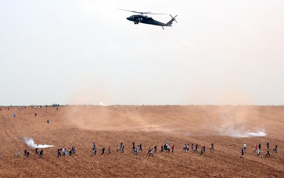 Un elicopter zboară deasupra unui câmp, în timp ce scutierii şi soldaţii turci se confruntă cu protestatarii, în timpul unei demonstraţii la Universitatea Dicle din Diyarbakir, marţi, 9 aprilie 2013. Studenţii kurzi de stânga au protestat după o ciocnire între grupurile de stânga şi de dreapta din Universitatea Dicle.