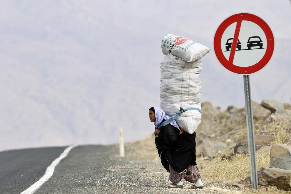 O femeie cară în spate un sac imens în timp ce se îndreaptă spre casă, în provincia Sirnak, aflată la graniţa turco-siriană, vineri, 9 noiembrie 2007.  Partidul Muncitorilor din Kurdistan se teme de un iminent atact turc asupra bazelor sale din nordul Irakului, după ce Statele Unite au declarat că vor ajuta Turcia să combată grupările separatiste.
