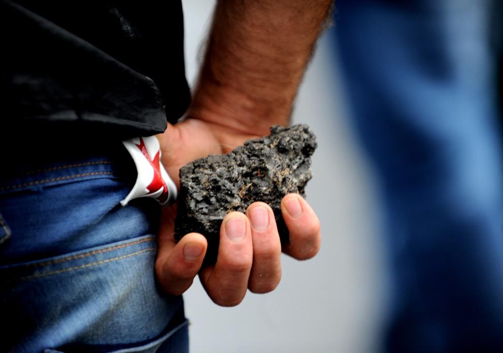 Un militant kurd ţine într-o mână o piatră în timpul ciocnirilor cu scutierii turci, în districtul Gazi din Istanbul, sâmbătă, 10 iulie 2010. Sute de kurzi au mărşăluit în semn de suport pentru Partidul Muncitorilor de Kurdistan (PMK) şi pentru a protesta împotriva uciderii a 12 militanţi PMK în ciocnirile de săptămâna trecută cu armata turcă.