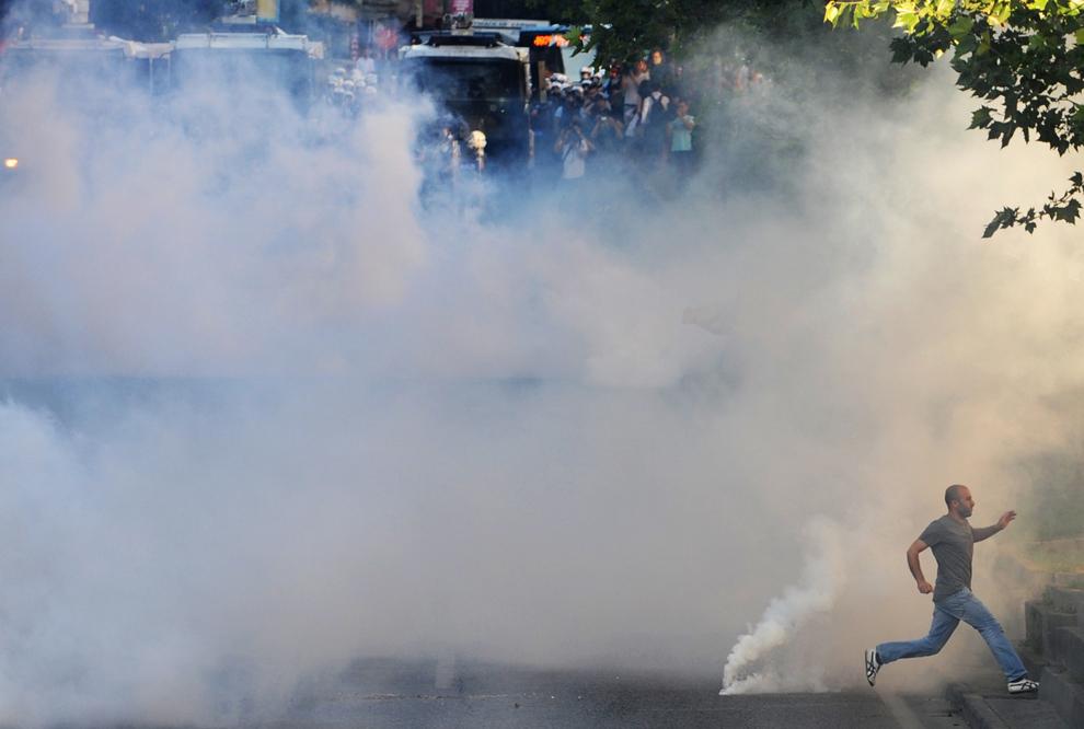 Un protestatar aleargă printr-un nor de gaz lacrimogen în timpul ciocnirilor dintre kurzi, turci de stânga şi scutieri, în Istanbul, miercuri, 22 iunie 2011. Parlamentarilor kurzi noi aleşi li s-a cerut să boicoteze sedinţele parlamentului turc după ce unui parlamentar i-a fost anulat mandatul câştigat la alegerile din 12 iunie datorită unei condamnări legate de terorism.