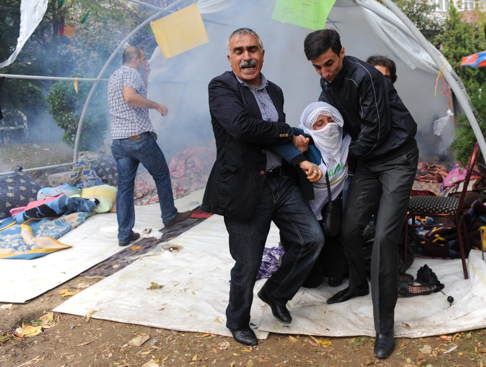 Doi protestatari ajută o femeie afectată de gazele lacrimogene folosite de către poliţişti în ciocnirile cu demonstranţii kurzi care manifestează în sprijinul prizonierilor kurzi aflaţi în greva foamei, în Istanbul, marţi, 30 octombrie 2012. Ministerul Justiţiei a declarat că 680 de prizonieri kurzi se află în greva foamei.