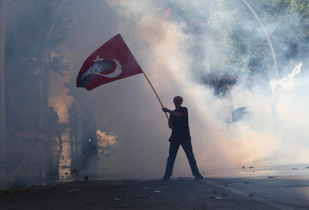 Un bărbat ce flutură un steag turcesc cu portretul fondatorului Turciei moderne Mustafa Kemal Ataturk este înconjurat de nori de gaze lacrimogene, în timpul unui protest în Ankara, Turcia, sâmbătă, 1 iunie 2013.