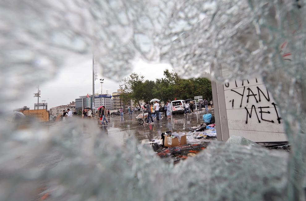 Protestatari pot fi văzuţi prin parbrizul spart al unei maşini, în timpul unui protest în Piaţa Taksim din Istanbul, Turcia, duminică, 2 iunie 2013.