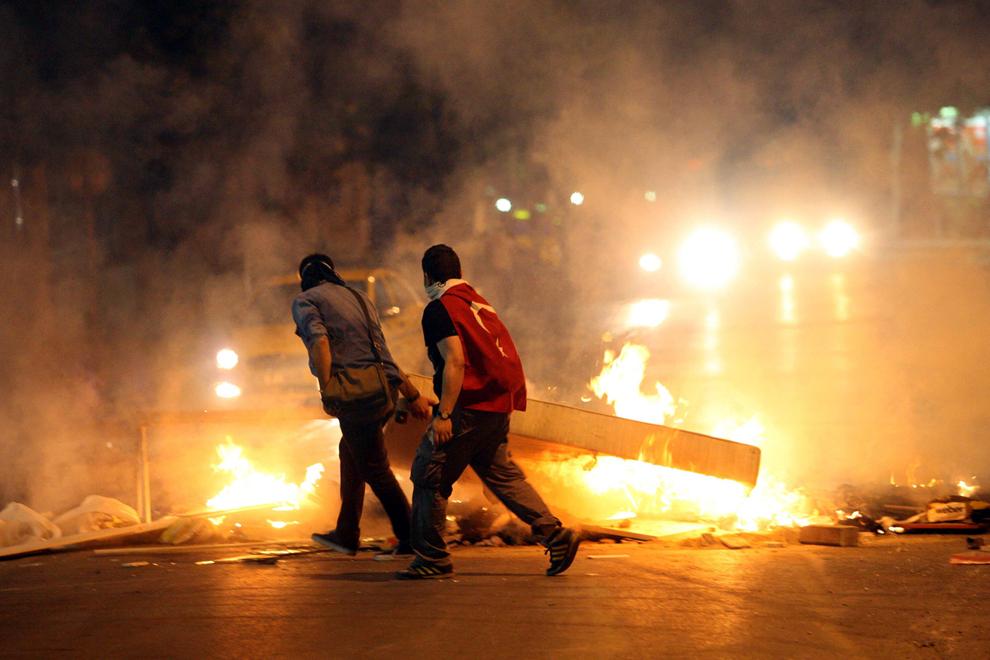 Protestatari cară o saltea ce a luat foc, în timpul unor lupte de stradă cu forţele de ordine, în Ankara, Turcia, luni, 3 iunie 2013.