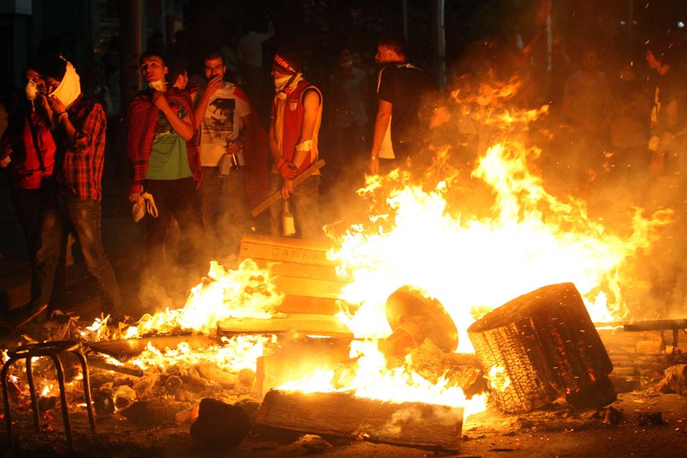 Protestatari privesc către mai multe obiecte ce au luat foc în timpul unor lupte de stradă cu forţele de ordine, în Ankara, Turcia, luni, 3 iunie 2013.
