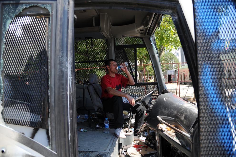 Un bărbat stă într-un  autobuz vandalizat, în timpul unui protest în Piaţa Taksim din Istanbul, Turcia, luni, 3 iunie 2013.