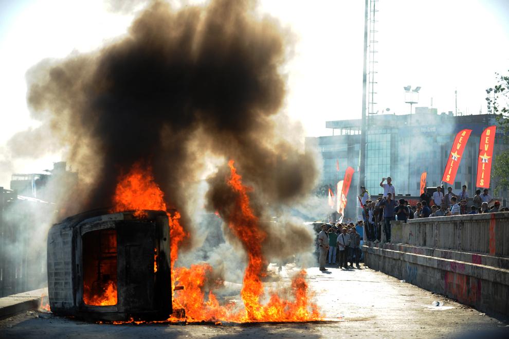 O maşină de poliţie ce a luat foc poate fi văzută în timpul unui protest, în Piaţa Taksim din Istanbul, Turcia, luni, 3 iunie 2013.
