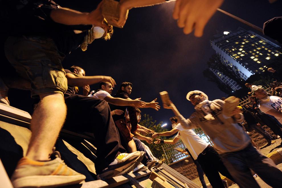 Protestatari fac un lanţ uman pentru a căra pietre folosite la construcţia unei baricade, în timpul luptelor de stradă cu forţele de ordine între Taksim şi Besiktas, Istanbul, Turcia, luni, 3 iunie 2013.