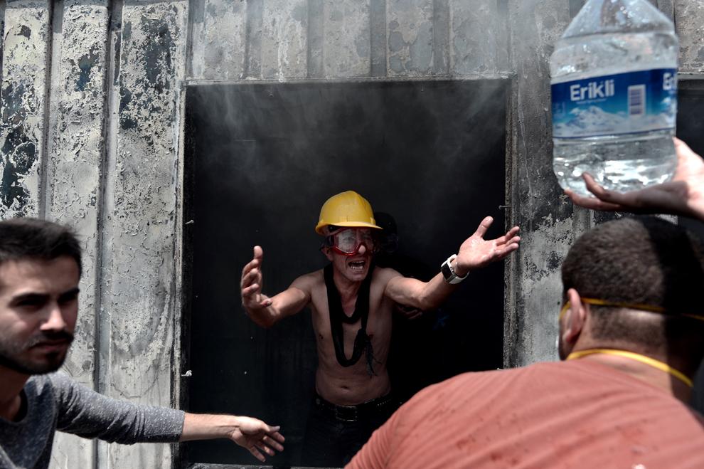 Mai multe persoane încearcă să stingă un container folosit de muncitorii în construcţii, în timpul unui protest, în Piaţa Taksim din Istanbul, Turcia, marţi, 4 iunie 2013.