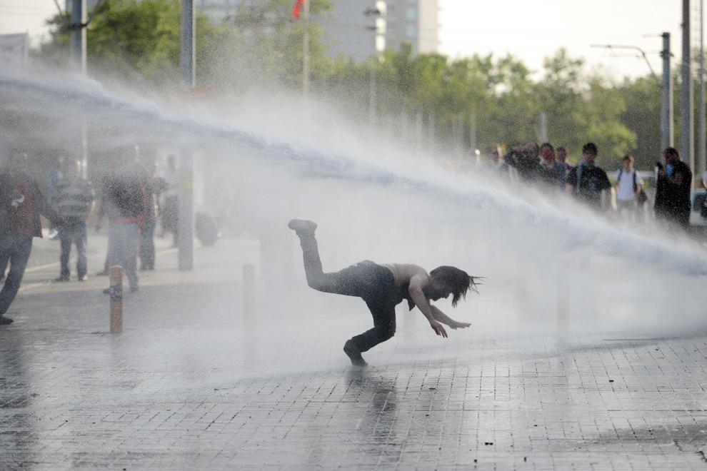 O persoană fuge din calea unui tun de apă, în timpul unor lupte stradale cu forţele de ordine, în Piaţa Taksim din Istanbul, Turcia, vineri, 31 mai 2013.