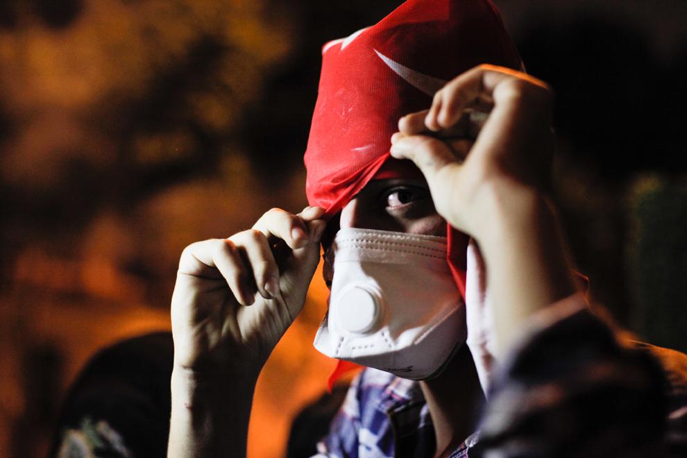 Un protestatar îşi acoperă faţa în timpul unor lupte de stradă cu forţele de ordine, în apropierea biroului prim-ministrului turc, Recep Tayyip Erdogan, între Taksim şi Besiktas, Istanbul, Turcia, luni, 3 iunie 2013.